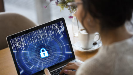 young lady looking at laptop showing padlock implying security