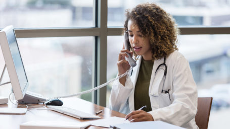The mid adult female doctor, sitting in her office, uses the landline to make phone calls regarding patient records.
